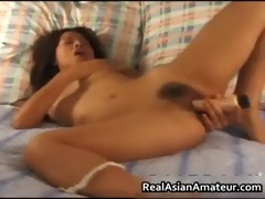 oriental nympho toying her hirsute pussy