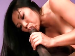 asian playgirl sits on a dark schlong and rides it
